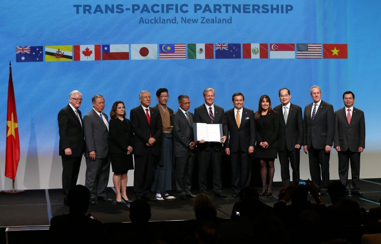 New Zealand Prime Minister John Key (6R) and Ministerial Representatives from 12 countries pose for a photo after signing the Trans-Pacific Partnership agreement in Auckland on February 3, 2016. / AFP / MICHAEL BRADLEY